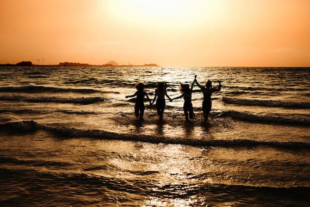 海で実行され、手を繋いでいる4人の女の子のシルエット。
