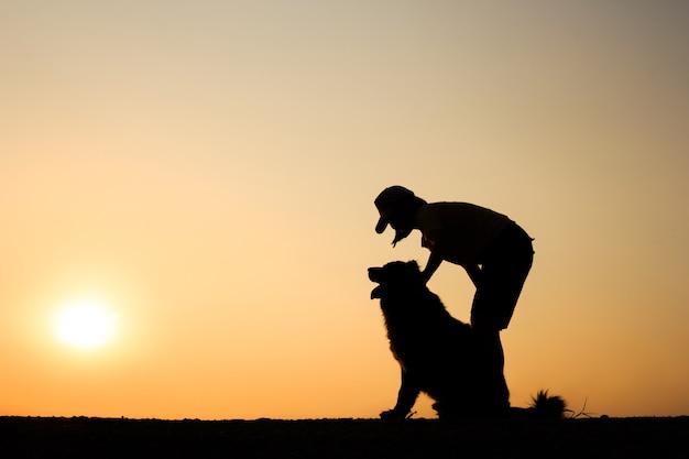 女の子と美しい夕日の背景と彼女の犬のシルエット。