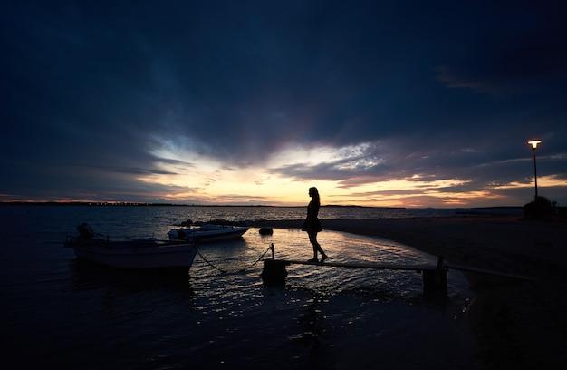 海の海岸で少女のシルエット