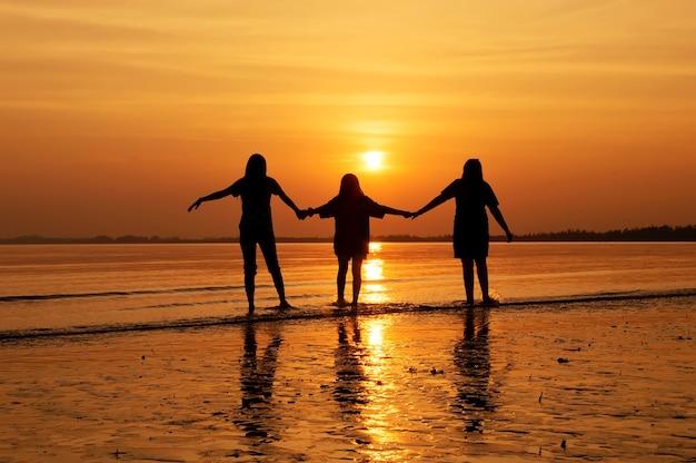 夕暮れのビーチで歩く手を持っている女の子グループのシルエット