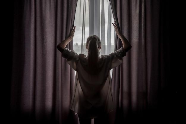 窓際の白人男性シャツの女の子のシルエット。カーテンを分けている素敵な女性の背面図。家の快適さ。スラブの女性は日光の下に立っています。感情とリラックス。コンセプトイメージ