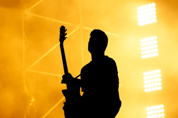 ギタリスト、ギタリストがコンサートステージで演奏するシルエット。オレンジ色の背景、煙、コンサートのスポットライト。