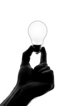 鈍い電球を持っている手のシルエット。白で隔離