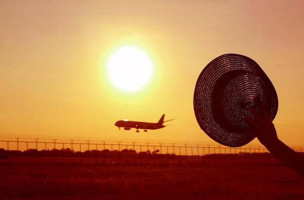 日の出の空に飛んでいる飛行機に手を振っている帽子を持っている手のシルエット