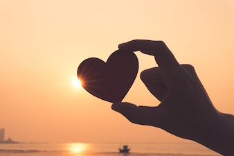 Silhouette of hand holding red heart during sunset background.