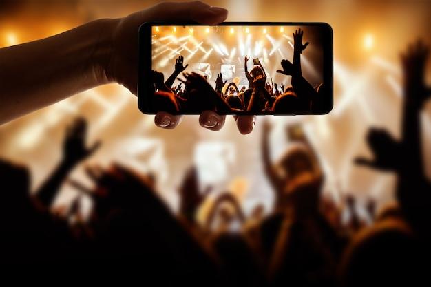 ポップコンサート、フェスティバルで写真やビデオを撮るためにカメラ付き携帯電話を使用して手のシルエット。
