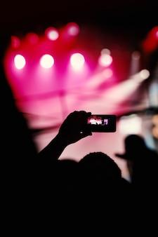 라이브 음악 쇼에서 사진과 비디오를 찍기 위해 스마트폰을 사용하는 손의 실루엣.