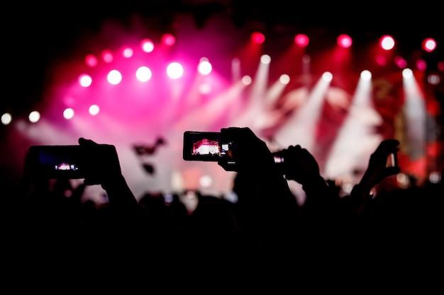 라이브 음악 쇼에서 사진과 비디오를 찍기 위해 스마트 폰을 사용하는 손의 실루엣.