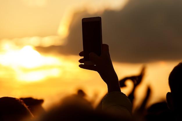 ライブミュージックショーで写真やビデオを撮るためにスマートフォンを使用している手のシルエット。