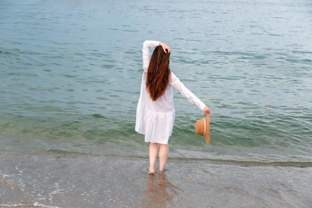 海のビーチで日没で休む白いビーチドレスの細い脚で後ろから幸せな楽しみの女性のシルエット。海岸で麦わら帽子を手に認識できない幸せな女性。