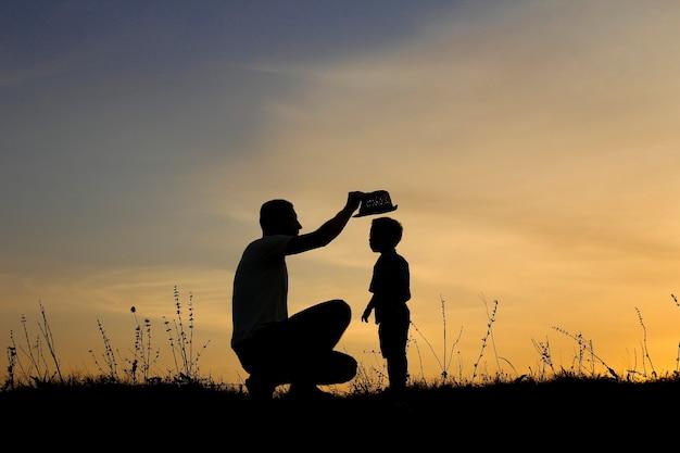 행복 한 아버지와 아들의 실루엣 일몰에 재생