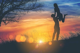 Silhouette of happy guy holding his girlfriend