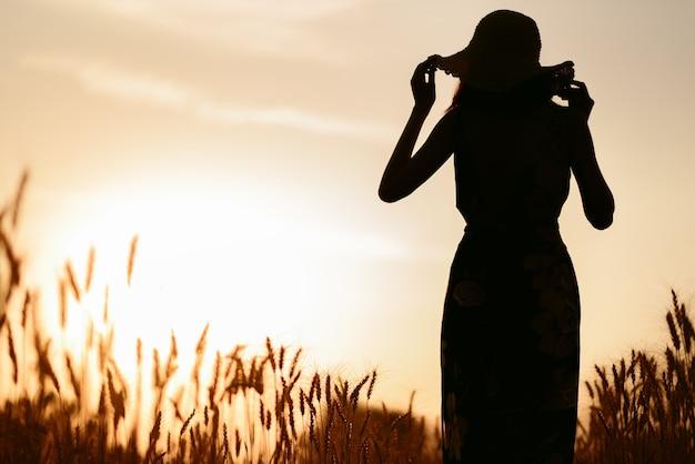 日没時の麦畑で幸せな女性のシルエット