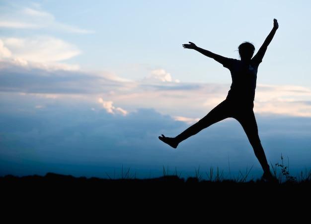 Силуэт счастливой женщины прыгает в зеленом поле против голубого неба.