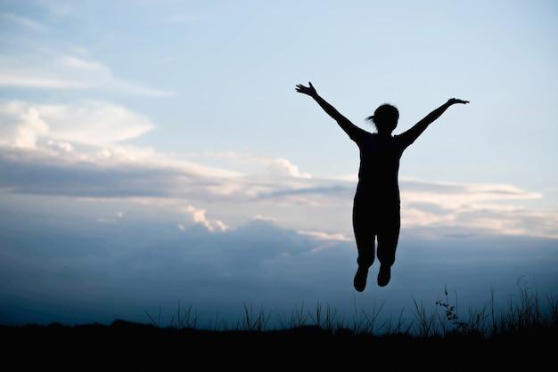 山の夕日に向かってジャンプ幸せな若い女性のシルエット
