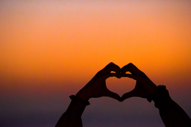 Силуэт сердца, сделанные детьми на закате
