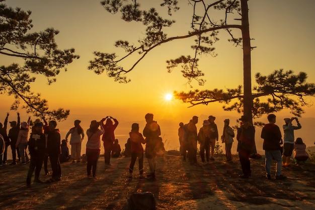 등산객의 실루엣은 언덕 꼭대기에서 일출을 즐깁니다.