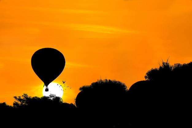 夕日の背景に熱気球のシルエット