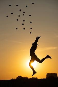 カラフルな夕日にボールとジャンプするジャグラーのシルエット