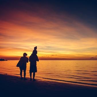 선셋 비치 휴가 휴가 여행 개념 밝은 다채로운 하늘에 사랑스러운 가족의 실루엣