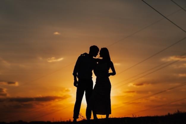 Силуэт влюбленной пары, стоящей на берегу реки. пара против красивого закатного неба.