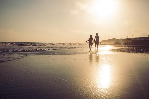 砂浜を歩いて夕日を楽しむ愛情のあるカップルのシルエット