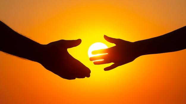 석양의 배경에 남성과 여성의 손의 실루엣. 의사 소통의 개념과 사회와 가족의 친밀감을 위해 노력합니다.