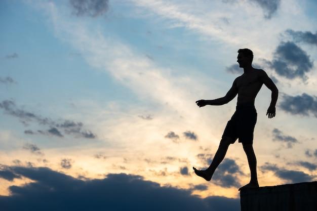 Силуэт человека против облаков и заката