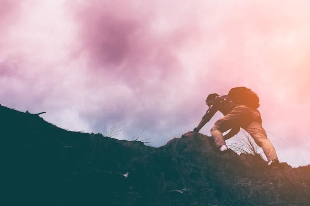 가파른 산을 등반하는 사람의 실루엣입니다. 모험, 투쟁 및 성공 스토리 사진을위한 좋은 이미지.