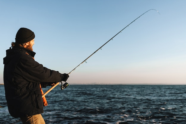 コートを着て、ロッドを保持し、ビーチで釣りをする男の漁師のシルエット