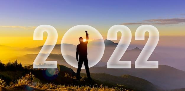 山の丘で2022年に挑戦する男のシルエット。明けましておめでとうございます2022年。日没時の男のシルエット、日の出は山のショーの変更、スタートアップ、目標、リーダーの概念で2022年と戦うために手を上げます