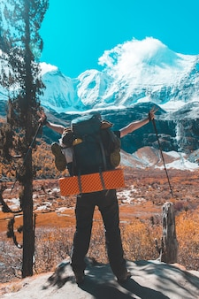 男のシルエットが成功のコンセプトの山の頂上に手を握る