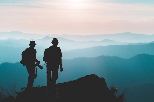 男のシルエットは、山、成功の概念のピークに手を握る