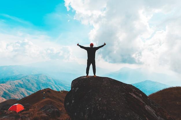 Силуэт человека держать руки на вершине горы