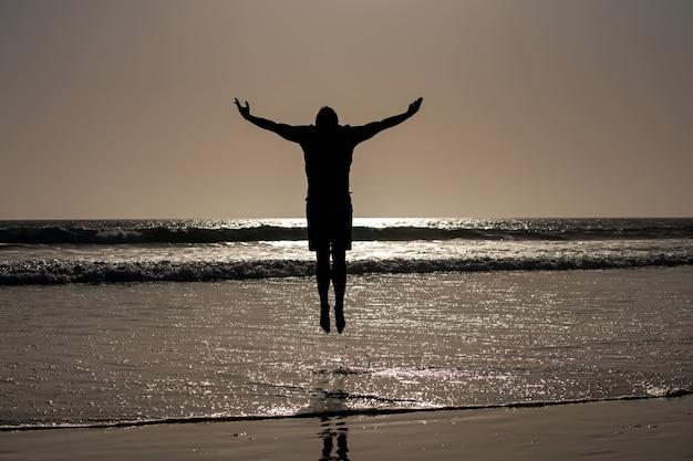 ビーチでジャンプする男のシルエット。サンセットビーチの素晴らしい景色。