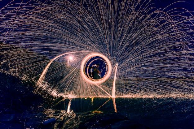 Силуэт человека делает круг искр в ночное время