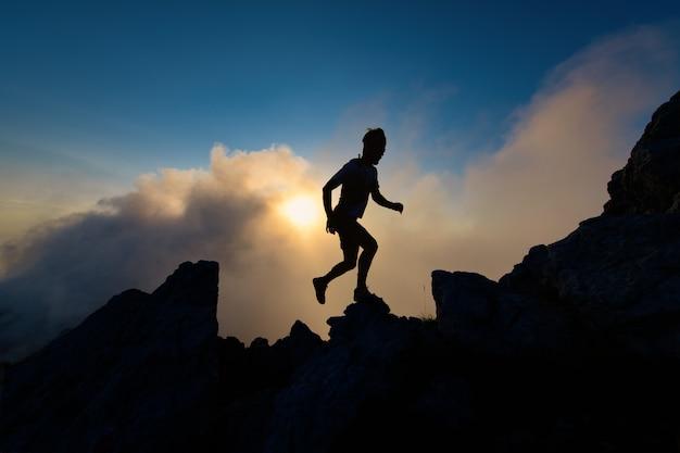 上り坂を実行している山の岩が多い尾根上の男のシルエット
