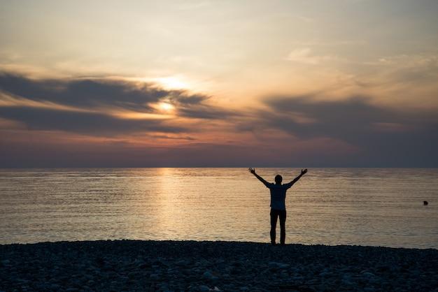 太陽が昇るとき彼の手または開いた腕を上げる男のシルエット