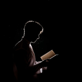 Silhouette of man reading in quran
