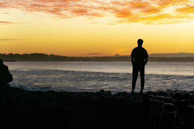 일몰 부 엉 바다와 산 배경을 보고 바위에 서 있는 남자의 실루엣.