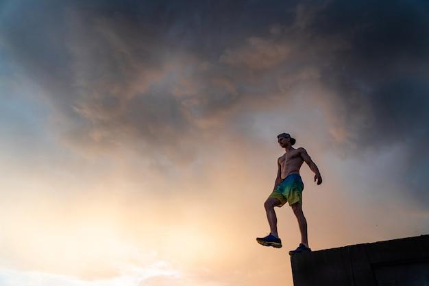 Силуэт человека, шагающего от края во время драматического заката. концептуальная цель, шаг вперед и риск
