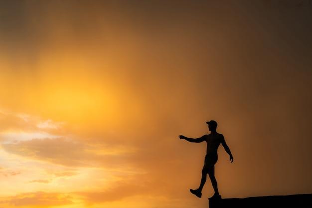 Силуэт человека, выходящего с края во время драматического заката, шаг вперед и цель концепции