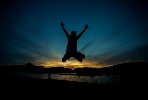 남자는 행복의 실루엣입니다. 자연광, 황금빛 저녁 빛, 마지막 빛.