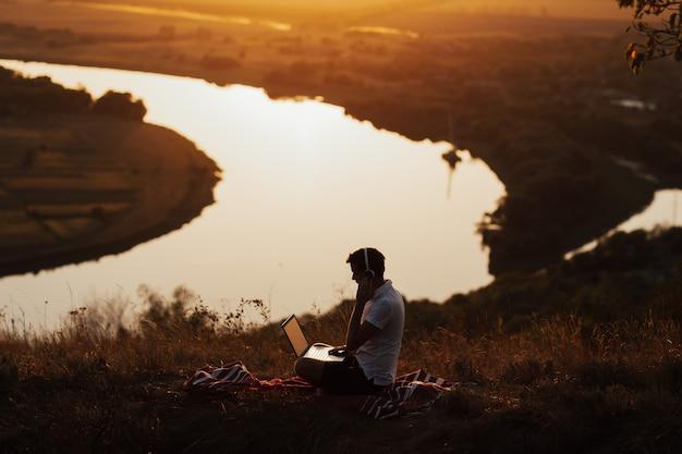 日没時の丘の上のコンピューターで作業する男のシルエット。