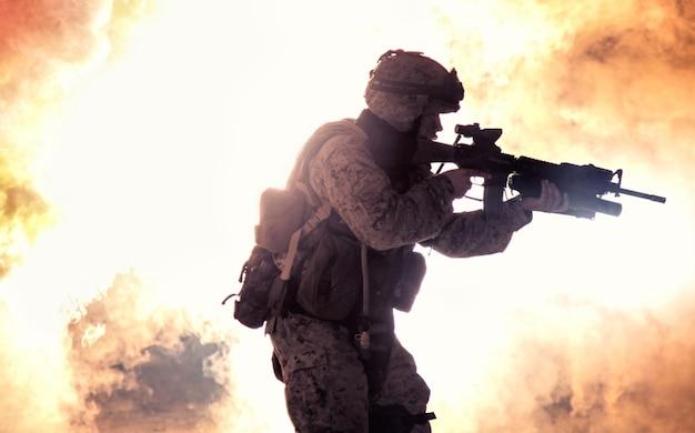 현대 보병 병사의 실루엣, 전술 탄약과 헬멧을 쓴 엘리트 육군 전투기, 불 같은 폭발의 배경에 돌격 소총을 들고 서 있습니다. 전쟁 충돌의 불타는 불