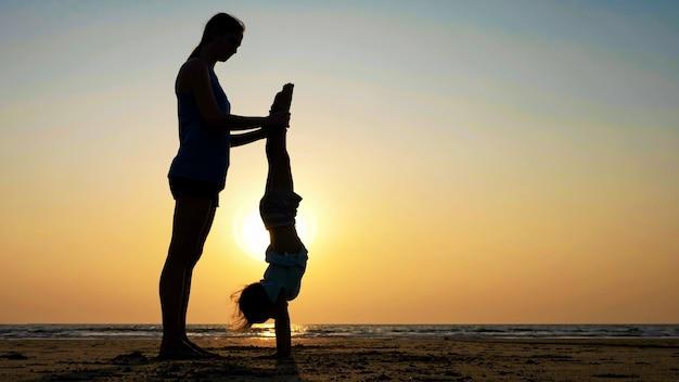夕暮れ時のビーチで体操をしている娘を持つ母のシルエット