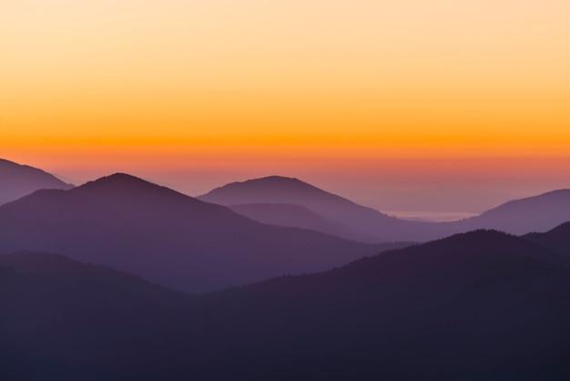 劇的な日の出の空と霞の山脈のシルエット。ソフトフォーカス。