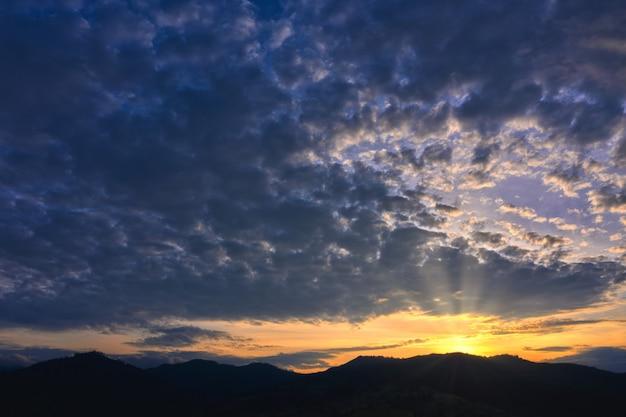 美しい雲と輝く太陽の劇的な背景に山のシルエット