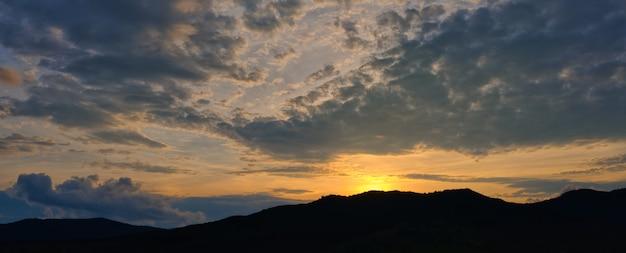 Силуэт гор с красивым закатом с ярким заходящим солнцем