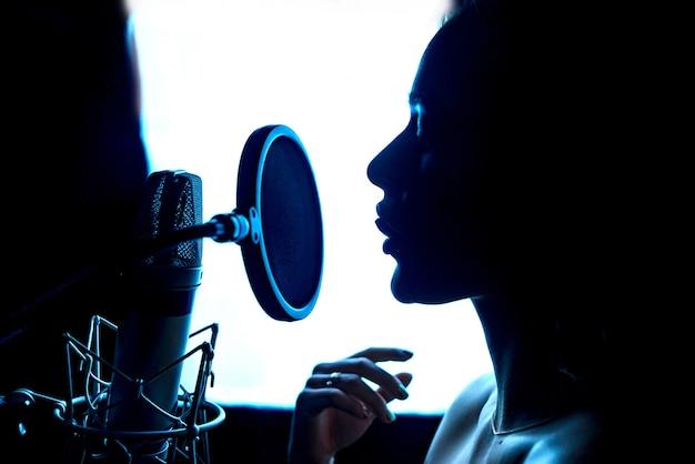 음악 열정적 인 여성과 전문 스튜디오에서 마이크의 실루엣. 마이크 앞에서 가수. 확대.